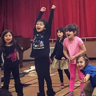 5 children performing in a school auditorium