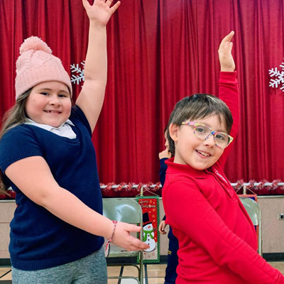 two children dancing in front of a red curtain
