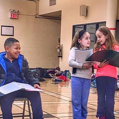 3 children reading from script book in a school gym